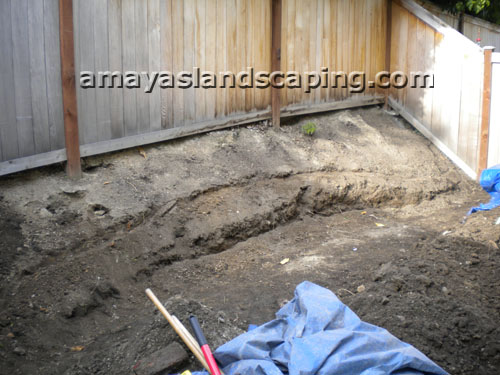 Backyard side area BEFORE patio, retaining walls, bark, and small plants