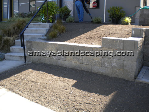 Sloped entry lawn BEFORE sod installation, with retaining wall installed.