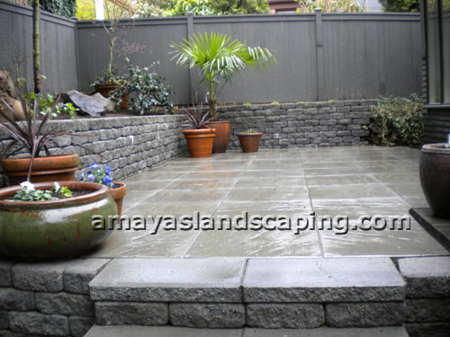 Patio area with steps AFTER installation of bricks, potted plants, and side retaining wall.